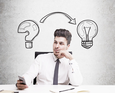 solves: Businessman sitting at table against concrete wall background with light bulb and question mark sketches on it. Concept of new idea search.