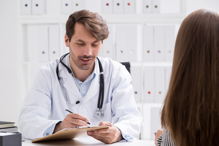 Doctor is writing down what patient has to say about her well being. Concept of attention to details.