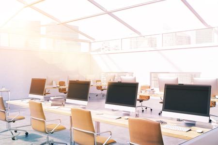 Kamer op zolder met veel computers op bureaus en witte muren. Stad gezien door glazen dak. Concept call center. 3D-weergave. Mock up. Getoonde afbeelding Stockfoto