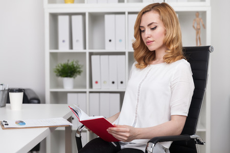 Woman in white shirt reading red book at office desk. Modern office interior. Concept of free time importance. Stock Photo