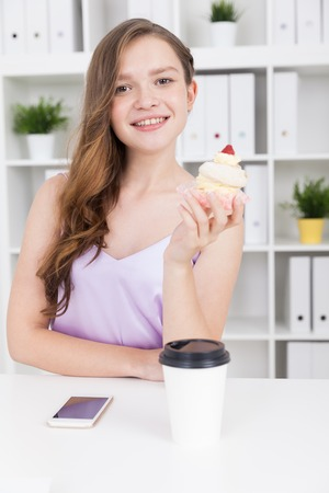 lunch hour: Girl holding cupcake and looking to camera smiling at her working place. Cell phone and coffee on desk. Lunch hour at office. Concept of tasty food break Stock Photo