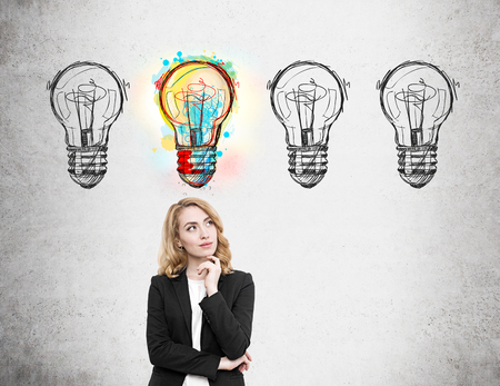 probability: Woman in suit standing near concrete wall with light bulb doodles and thinking. One out of four lbulbs is lit. Concept of high probability