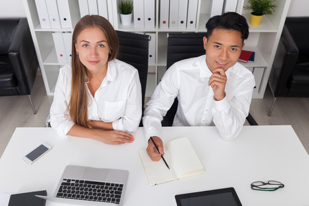 cutting edge: Smiling people at their desk. Modern office with good furniture and cutting edge gadgets. Concept of good firm Stock Photo