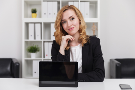 Business lady smiling to camera. Tablet is standing on desk in front of her with screen turned to viewer. Smart phone on table. Concept of devices at work. Mock up