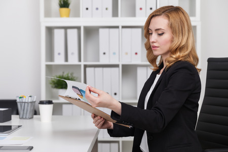 confident business woman: Woman with clipboard sitting at her desk and examining document. Concept of work with information