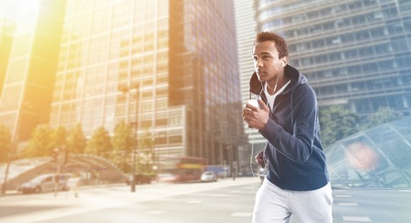 African American man jogging in business district in London at morning time. Concept of healthy way of life importance. Toned image