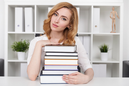 law school: Woman with pile of books looking possessive. Concept of university literature course and knowledge value in modern society Stock Photo