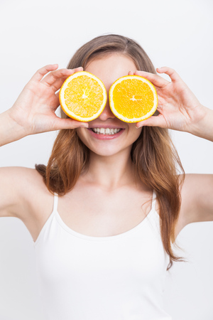 cuteness: Smiling girl holding orange halves near her face. Concept of beauty and cuteness. Organic fitness