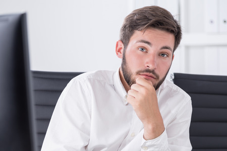 fortunate: Young successful businessman portrait. He is sitting in boardroom in white shirt. One hand near chin. Concept of fortunate entrepreneur