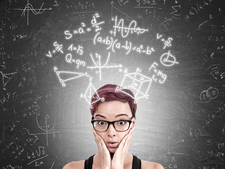 exact: Woman with red hair and glasses standing against blackboard with formulas and sketches. Concept of exact sciences and their complexity Stock Photo