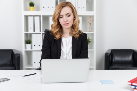 advise: Businesswoman with wavy hair wearing suit working with her laptop in office. Concept of entrepreneurship Stock Photo