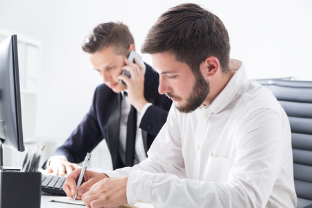 one on one meeting: Two businessmen working in their company office. One is talking on cell phone. Second is writing his ideas for future board meeting. Concept of busy people