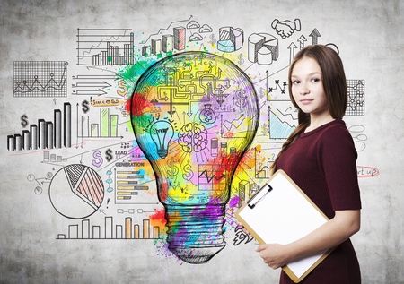 Young woman with clipboard is standing near concrete wall with colorful light bulb sketch. Concept of business idea. Mock up Stock Photo