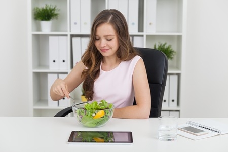 Woman eating salad in office. She is enjoying it while tablet, glass of water and smart phone lie on desk beside her. Bookcase with binders at background. Concept of healthy food consumption Stock Photo