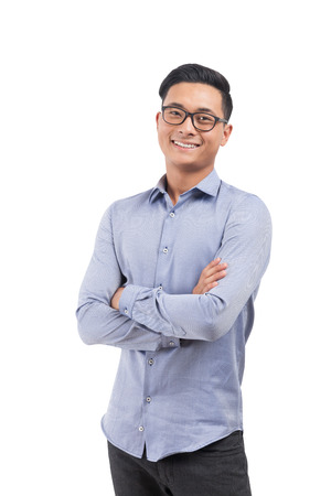Smiling Asian man in glasses, blue shirt and black pants standing with hands folded. Concept of engineering jobs