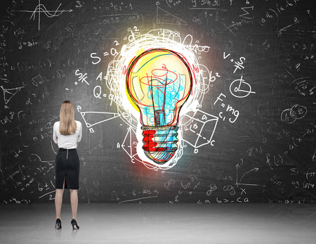 exact science: Woman with blond hair standing with back to viewer and looking at giant colorful light bulb sketch on blackboard. Concept of science discovery. Stock Photo