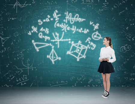 exact: Woman with tablet standing near blue green chalkboard looking at complex formulas. Concept of exact sciences Stock Photo