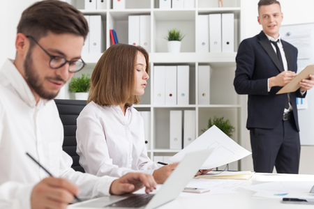 advise: Brainstorming in modern company. People at table. One man making statement in front of colleagues. Concept of team work Stock Photo