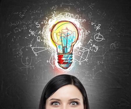 Close-up Womans hoofd tegen het bord met kleurrijke schets gloeilamp omgeven door formules. Het concept van de nieuwe oorspronkelijke idee Stockfoto