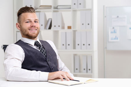 Young office worker sitting at his table and smiling broadly to camera in office room with binders on shelves and white board. Concept of work