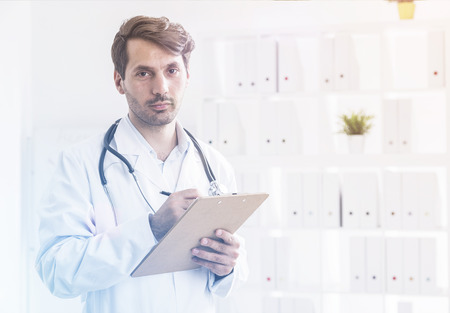 family practitioner: Portrait of family doctor with clipboard and stethoscope standing in his office in looking concentrated. Concept of good practitioner. Toned image Stock Photo