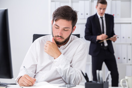 businessman signing documents: Businessman signing documents in his office. His colleague in background making notes in clippad. Concept of busy day