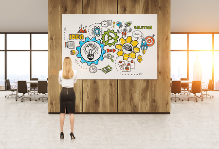 businesswoman standing: Office interior. Businesswoman standing with back to camera examining whiteboard with abstract sketches pictured on it. Concept of startup foundation. 3d rendering. Toned image