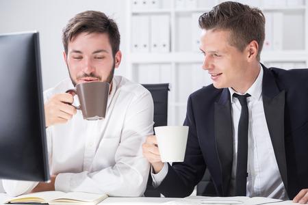 Due soci che lavorano insieme al tavolo del calcolatore. Bere il caffè e godersi la conversazione. Concetto di unione commerciale di successo