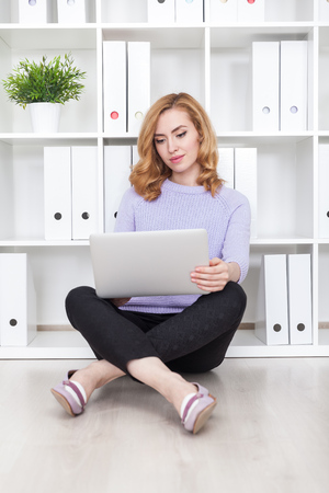 Serious woman sitting on office floor with her large white tablet and legs crossed. Concept of doing job well Reklamní fotografie