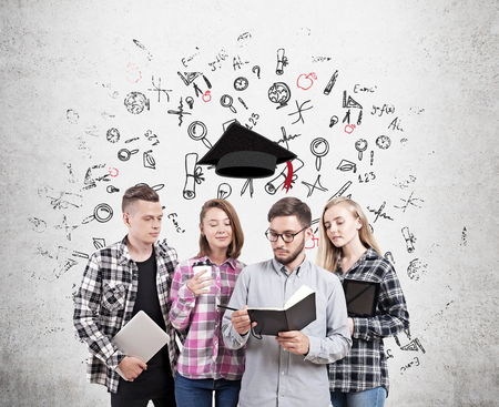 finishing school: University students standing near concrete wall with sketches on it with graduation hat floating above them. Concept of finishing school and starting adult life.