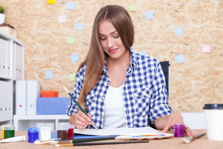 big picture: Nice girl with long blond hair is painting in her album. She is sitting at her workplace with table, cork board and book shelves. Concept of sketching for big picture