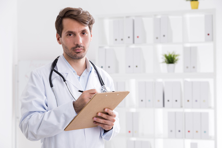 Doctor with clipboard taking notes and looking to camera while standing in his office. Concept of attentive specialist Stock Photo