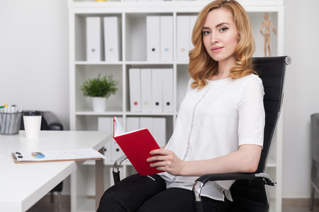 lunch hour: Woman with red book sitting at office desk. Shelves with binders in background. Concept of leisure time at lunch hour.