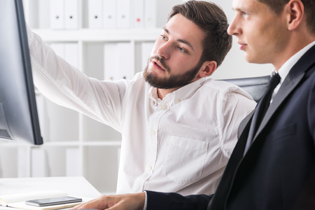 discovered: Businessman in shirt showing his colleague what he has discovered in companys bookkeeping documents. Concept of scrupulous work Stock Photo