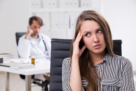 molesto: El doctor está teniendo conversación telefónica mientras se patien parece aburrido y esperando a que terminara el examen