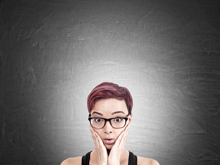 powerless: Confused woman standing near blackboard. Concept of challenging task ahead. Mock up Stock Photo