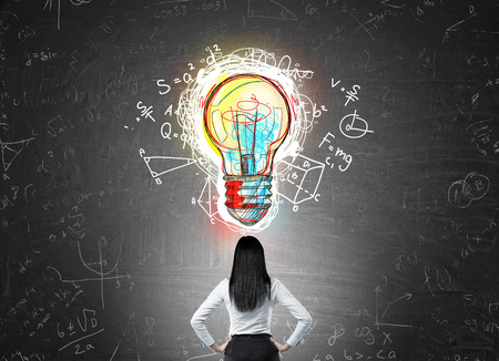 exact science: Woman with black hair in suit standing with back to camera looking at light bulb sketch on chalk board. Concept of science discovery Stock Photo