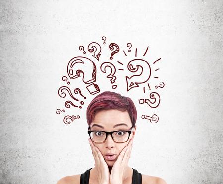 Mujer de cerca con dibujos de signo de interrogación en la pared de hormigón. Concepto de que tiene demasiadas preguntas