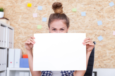 Smiling girl with piece of paper looking to camera holding sheet near her face. Concept of playful product ad. Mock up