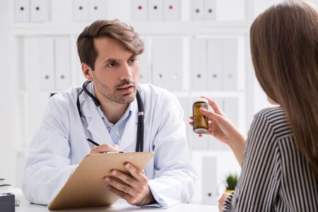 prescribed: Doctor is writing and observing patient. She is looking at prescribed pill bottle. Concept of right medication importance Stock Photo