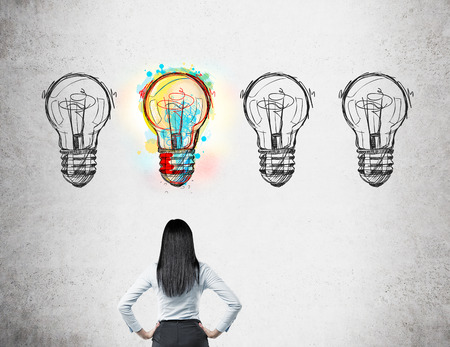 probable: Woman with black hair standing with her back to viewer looking at four light bulb doodles drawn on wall. Only one of them is bright. Concept of good chance and choice.