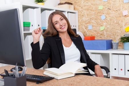 broadly: Cheerful business lady smiling broadly to camera while sitting in her office. Concept of good mood is key to productivity