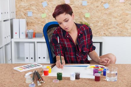 Frau Maler bei der Arbeit im College-Büro. Kork Bord an der Wand. Palette und Farbe liegen auf dem Schreibtisch. Konzept der Hochschulbildung in Kunst und Skulptur.