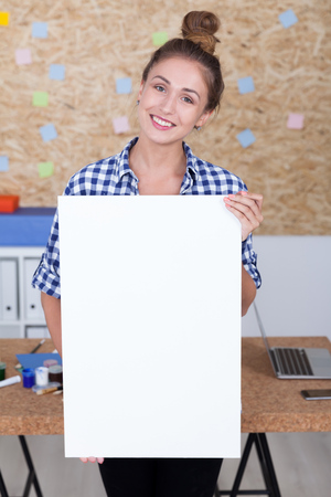 big cork: Girl with bun in checkered shirt is standing in her office with large blank piece of paper. Concept of advertisement. Mock up