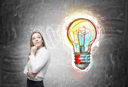 new idea: Businesswoman standing near blackboard with colorful light bulb sketch pictured on it. Concept of new idea and business development
