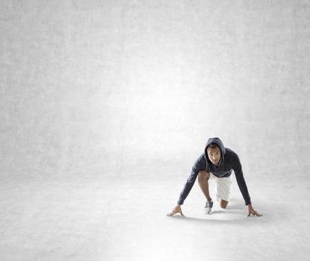 competitividad: African American joven se está preparando para correr en el sitio de la pared de hormigón. Concepto de planificación de corta distancia. Bosquejo