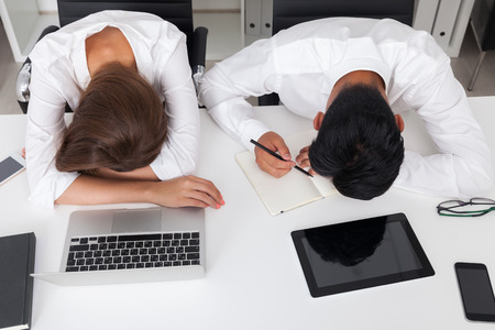 sleeping tablets: Very tired office workers at laying head on hands on their desk. Concept of desperate need of sweet weekend. Top view