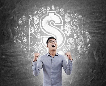 dollar signs: Excited Asian man standing against blackboard with dollar signs drawn on it. Concept of money earning