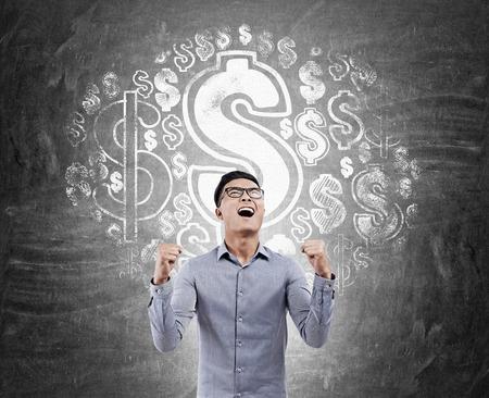signos de pesos: Hombre asiático emocionado de pie contra la pizarra con signos de dólar en lo. Concepto de ganar dinero Foto de archivo