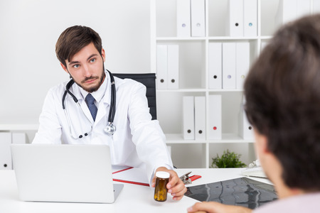 general practice: Doctor with beard is giving jar of pills to his patient. Concept of modern pharmacology and medicine limits